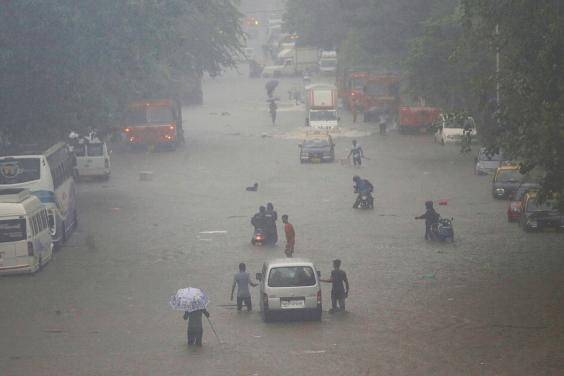 Commuters navigating a flooded street in Mumbai after heavy rainfall in September (Reuters)