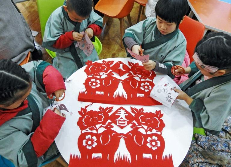Children learning traditional paper cutting ahead of the Lunar New Year, the Year of the Pig, in Lianyungang in China's eastern Jiangsu province