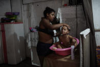 Thayane, who made a living as a manicurist before the coronavirus pandemic hit, bathes her 3-year-old daughter Melyssa in their room of an occupied building where she lives with her three daughters in Rio de Janeiro, Brazil, Thursday, March 11, 2021. During the pandemic, more than 6.5 million Brazilian women exited the workforce, dropping their participation rate below 48% — the lowest in more than a decade. (AP Photo/Silvia Izquierdo)
