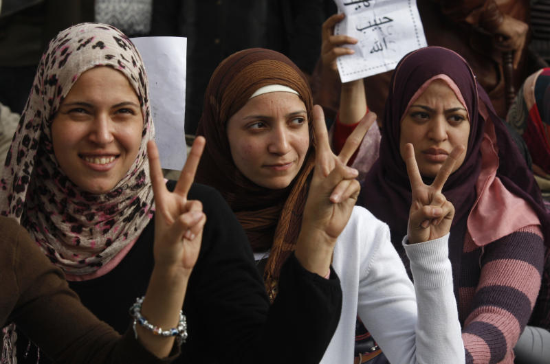 Three women gesture for victory  as they attend a demonstration in Cairo, Egypt, Sunday Jan.30, 2011. Minutes before the start of a 4 p.m. curfew, at least two jets appeared and made multiple passes over downtown, including a central square where thousands of protesters were calling for the departure of President Hosni Mubarak. (AP Photo/Khalil Hamra)