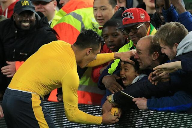 Arsenal's striker Alexis Sanchez gives his match shirt to a young fan following a win over Middlesbrough on April 17, 2017 (AFP Photo/Lindsey PARNABY)