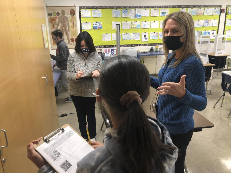 Jennifer Becker, right, Science Teacher at the Sinaloa Middle School, talks to one of her students in Novato, Calif. on Tuesday, March 2, 2021. The school just reopened Monday, Feb. 22, 2021 for in-person learning. (AP Photo/Haven Daily)