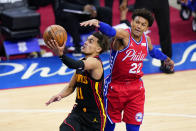 Atlanta Hawks' Trae Young, left, goes up for a shot past Philadelphia 76ers' Matisse Thybulle during the second half of Game 1 of a second-round NBA basketball playoff series, Sunday, June 6, 2021, in Philadelphia. (AP Photo/Matt Slocum)