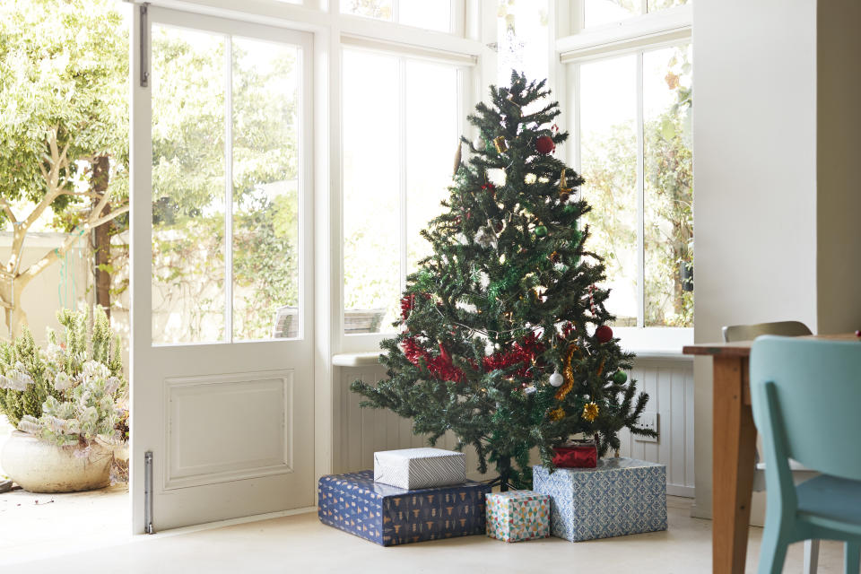 Christmas tree with gift boxes by window at entrance of house