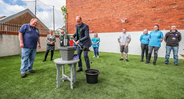 Britain's Prince William, Duke of Cambridge (C) plants a tree in a pot during his visit to Brighter Futures, a consortium of eight local groups which encourage loal people to participate in community activities, in Rhyl, Denbighshire, Wales on May 6, 2021. (Photo by Peter Byrne / POOL / AFP) (Photo by PETER BYRNE/POOL/AFP via Getty Images)