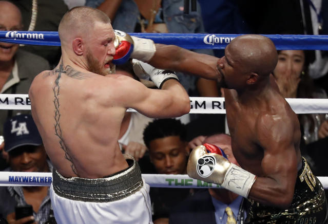 Floyd Mayweather Jr. lands against Conor McGregor in their boxing match Saturday night in Las Vegas. (AP)