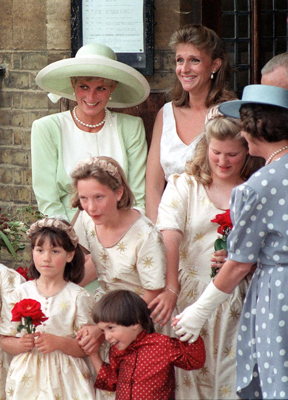 PA NEWS PHOTO 30/8/91  DIANA, THE PRINCESS OF WALES AT THE WEDDING OF HER FORMER FLAT-MATE VIRGINIA PITMAN TO BANKER HENRY CLARKE AT CHRIST CHURCH IN CHELSEA, LONDON. WITH HER IS ANOTHER OF HER OLD FLAT-MATES SOPRANO CAROLYN BARTHOLOMEW   (Photo by Martin Keene - PA Images/PA Images via Getty Images)