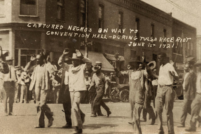 In this photo provided by the Department of Special Collections, McFarlin Library, The University of Tulsa, a group of Black men are marched past the corner of 2nd and Main Streets in Tulsa, Okla., under armed guard during the Tulsa Race Massacre on June 1, 1921. On May 31, 1921, carloads of Black residents, some of them armed, rushed to the sheriff's office downtown to confront whites who were gathering apparently to abduct and lynch a Black prisoner in the jail. Gunfire broke out, and over the next 24 hours, a white mob inflamed by rumors of a Black insurrection stormed the Greenwood district and burned it, destroying all 35 square blocks. Estimates of those killed ranged from 50 to 300. (Department of Special Collections, McFarlin Library, The University of Tulsa via AP)