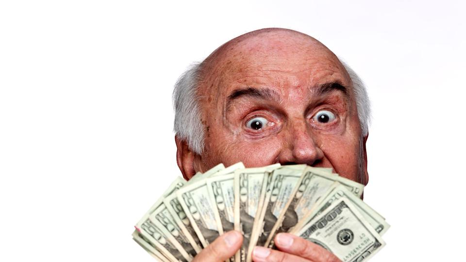 picture of elderly man holding a fan of money in front of his face