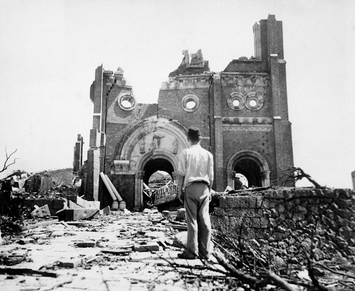 FILE - In this Sept. 13, 1945, file photo, the Urakami Catholic Cathedral in Nagasaki, Japan, stands waste in the aftermath of the detonation of the atom bomb over a month ago over this city. Many residents of Hiroshima welcome attention to their city from abroad, which IOC President Thomas Bach will bring when he visits on Friday, July 16. But Bach will also bring political baggage — as will his vice president John Coates when he visits Nagasaki the same day — that is largely unwelcome in two cities viewed as sacred by many Japanese.(AP Photo/Stanley Troutman, Pool, File)