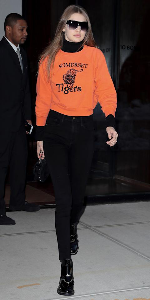 "<p>The model added a pop of color to her otherwise all-black outfit with an orange sweatshirt reading ""Somerset Tigers"" (get your own orange pullover <a rel=""nofollow"" href=""https://click.linksynergy.com/fs-bin/click?id=93xLBvPhAeE&subid=0&offerid=390098.1&type=10&tmpid=8158&RD_PARM1=http%253A%252F%252Fshop.nordstrom.com%252Fs%252Ftopshop-boutique-balloon-sleeve-sweatshirt%252F4609452&u1=ISGigiHadidStreetStyle3.17JA"">here</a>). She wore it over a black turtleneck and paired with black jeans from Frame Denim ($209; <a rel=""nofollow"" href=""https://click.linksynergy.com/fs-bin/click?id=93xLBvPhAeE&subid=0&offerid=484990.1&type=10&tmpid=23604&RD_PARM1=https%253A%252F%252Fwww.shopbop.com%252Fforever-karlie-skinny-jeans-frame%252Fvp%252Fv%253D1%252F1597251282.htm%253FfolderID%253D18389%2526fm%253Dother-shopbysize-viewall%2526os%253Dfalse%2526colorId%253D10652&u1=ISGigiHadidStreetStyle3.20JA"">shopbop.com</a>) and patent leather booties. </p>"