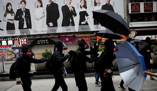 Demonstrators protect themselves with umbrellas during a protest in Hong Kong. Photo: Reuters