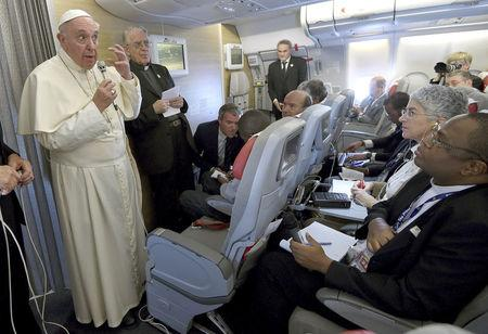 Pope Francis gestures during a meeting with the media onboard the papal plane while en route to Rome, Italy, November 30, 2015.   REUTERS/Daniel Dal Zennaro/Pool/File Photo