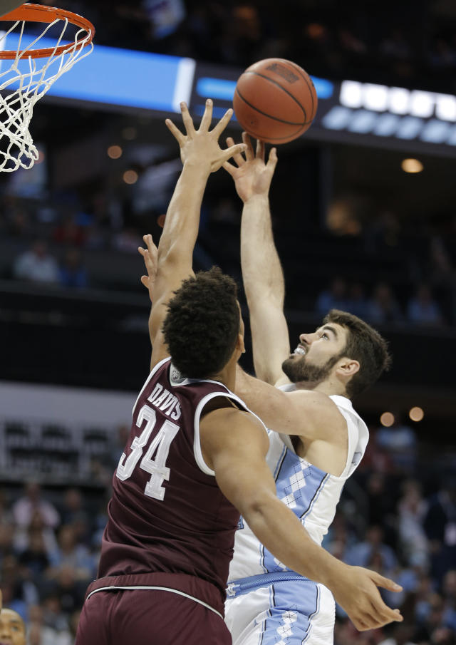 North Carolina's Luke Maye, right, shoots over Texas A&M's Tyler Davis (34) during the first half of a second-round game in the NCAA men's college basketball tournament in Charlotte, N.C., Sunday, March 18, 2018. (AP Photo/Bob Leverone)