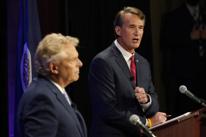 Republican gubernatorial candidate Glenn Youngkin, right, gestures as Democratic gubernatorial candidate and former governor Terry McAuliffe, left, looks on during a debate at the Appalachian School of Law in Grundy, Va., Thursday, Sept. 16, 2021. (AP Photo/Steve Helber)