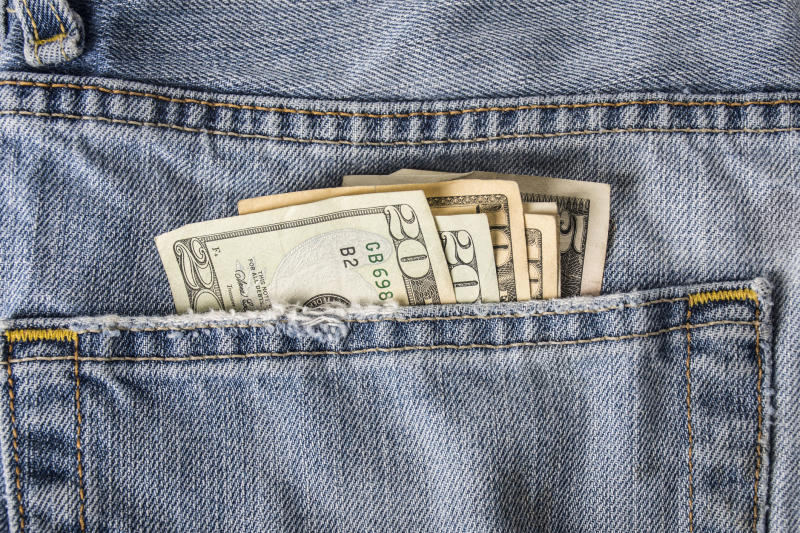 Cash sticking out from a jeans back pocket.