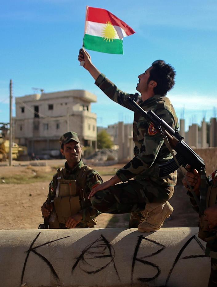 Kurdish Peshmerga fighters pose for a picture during a break in fighting against Islamic State jihadists in the Syrian border town of Kobane, on November 8, 2014 (AFP Photo/Ahmed Deeb)