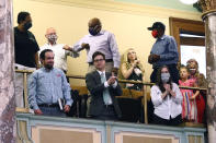 Observers in the gallery applaud after the Senate voted to change the Mississippi flag Sunday, June 28, 2020, at the Capitol in Jackson, Miss. Mississippi lawmakers voted to surrender the Confederate battle emblem from the flag, triggering raucous applause and cheers more than a century after white supremacist legislators adopted the design a generation after the South lost the Civil War. Republican Gov. Tate Reeves has said he will sign the bill, and the state flag would lose its official status as soon as he signs the measure. (AP Photo/Rogelio V. Solis)