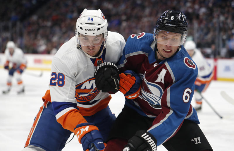 New York Islanders left wing Michael Dal Colle, left, and Colorado Avalanche defenseman Erik Johnson pursue the puck into the corner during the second period of an NHL hockey game Wednesday, Feb. 19, 2020, in Denver. (AP Photo/David Zalubowski)