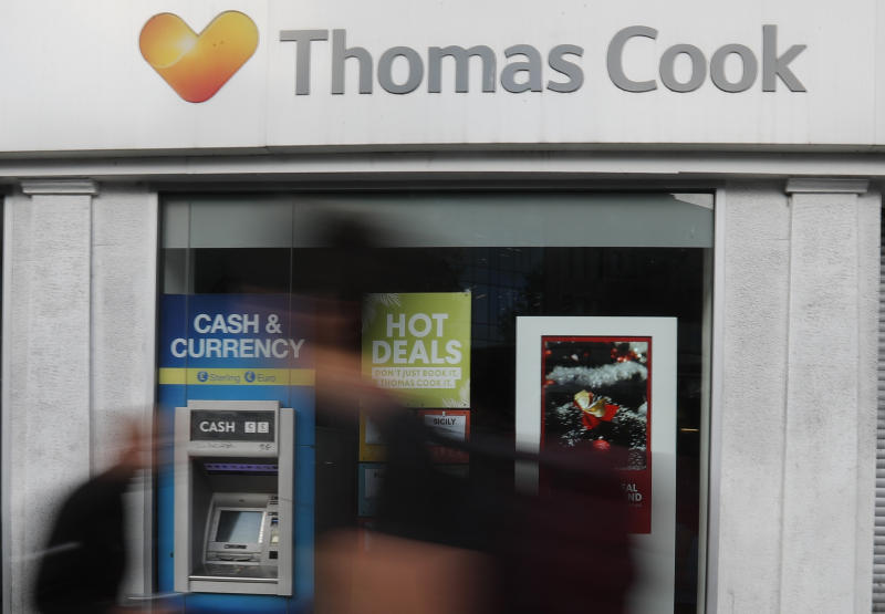 People walk past a closed Thomas Cook travel shop in London, Monday, Sept. 23, 2019. British tour company Thomas Cook collapsed early Monday after failing to secure emergency funding, leaving tens of thousands of vacationers stranded abroad. (AP Photo/Frank Augstein)