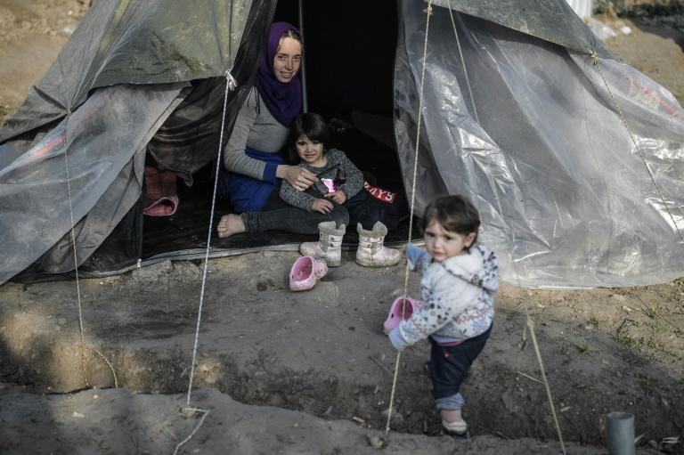 A Syrian woman sits in her tent with her children in the Vial refugee camp, on the Greek island of Chios, which is overcrowded with 5,000 people