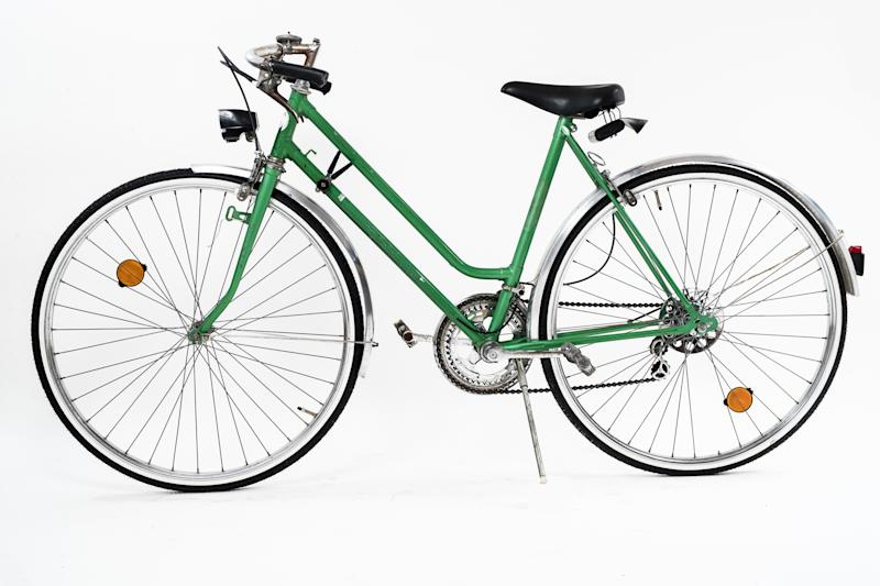 An old retro looking green vintage city bicycle for women, isolated o white background. Side view