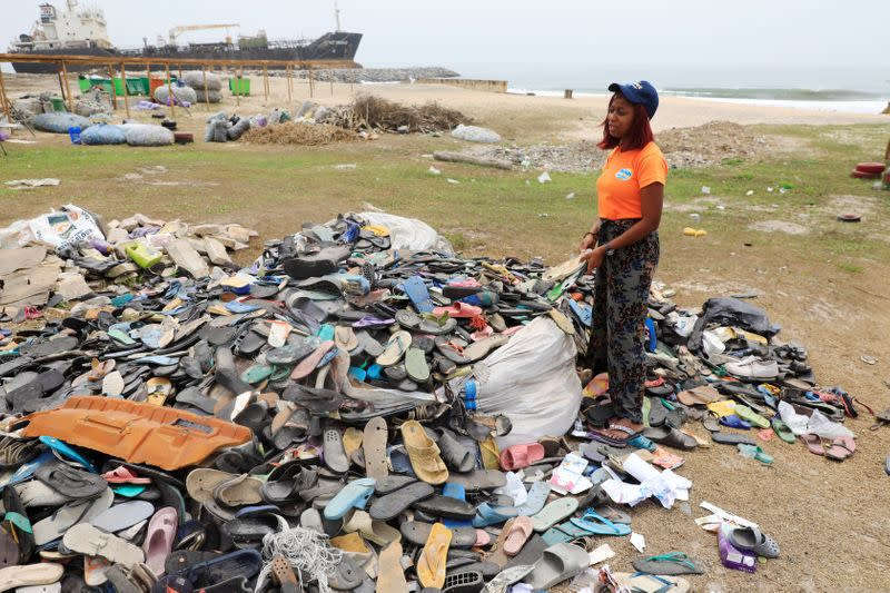 An Environmentalist, Doyinsola Ogunye stands in front of a heap of footwear picked from the shore at the beach in Lagos