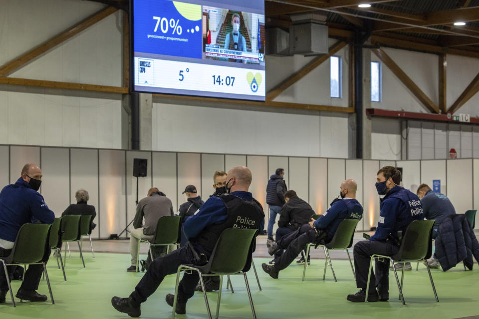 FILE - In this March 4, 2021, file photo, police officers and others sit in a waiting zone after receiving their COVID-19 vaccine at the Brussels Expo center in Brussels. In both the U.S. and the EU, officials are struggling with the same question: how to boost vaccination rates to the max and end a pandemic that has repeatedly thwarted efforts to control it. In the European Union, officials in many places are requiring people to show proof of vaccination, a negative test or recent recovery from COVID-19 to participate in everyday activities — even sometimes to go to work. (AP Photo/Olivier Matthys, File)