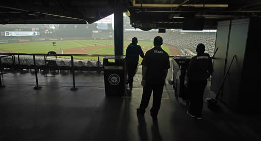 Members of T-Mobile Park's custodial and facilities team pause to watch the action during the first baseball game of a doubleheader between the Seattle Mariners and the Oakland Athletics, Monday, Sept. 14, 2020, in Seattle. (AP Photo/Ted S. Warren)
