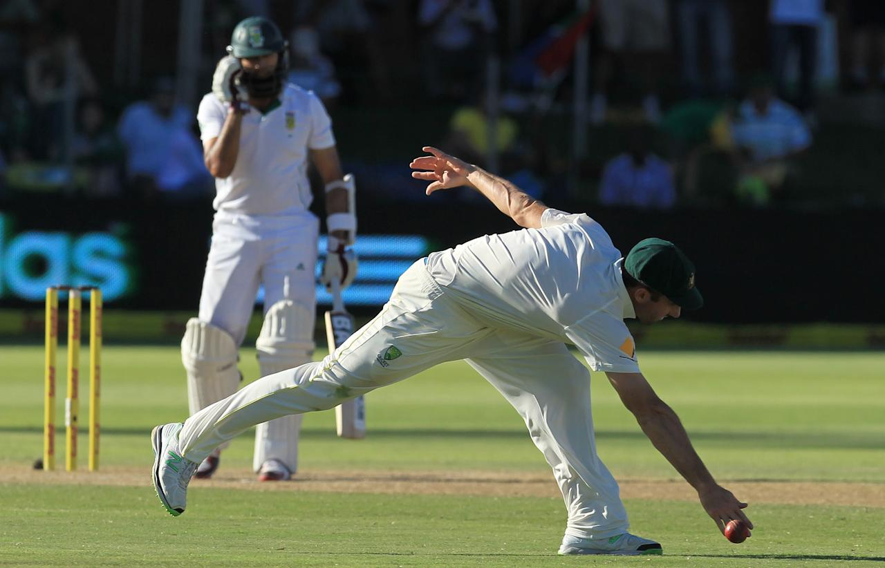 South Africa's batsman Hashim Amla, left, watches as Australia's Alex Doolan, right, attempts fielding his shot on the third day of their 2nd cricket test match at St George's Park in Port Elizabeth, South Africa, Saturday, Feb. 22, 2014. (AP Photo / Themba Hadebe)