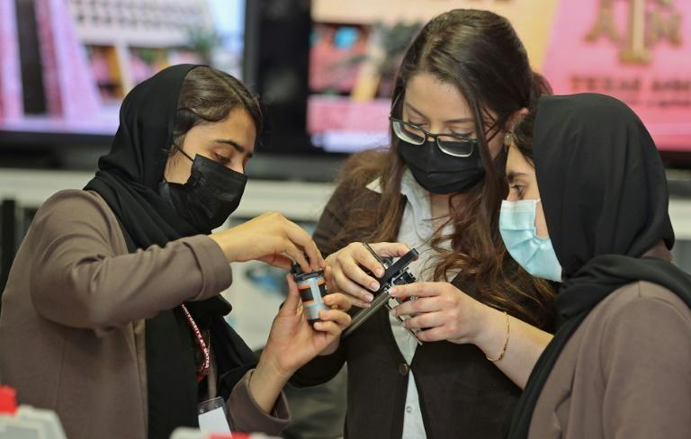 The nine members of an all-girl Afghan robotics team evacuated from Kabul to Qatar have acquired star status and captured hearts since fleeing their homeland (AFP/KARIM JAAFAR)