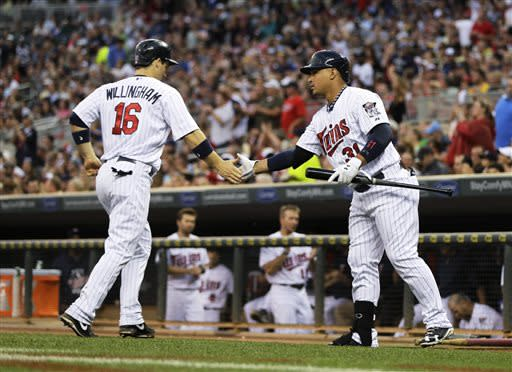 Minnesota Twins' Josh Willingham, left, is congraulated by Oswaldo Arcia after Willingham scored on a Justin Morneau double off Kansas City Royals' Humberto Quintero in the fourth inning of a baseball game Friday, June 28, 2013, in Minneapolis. (AP Photo/Jim Mone)