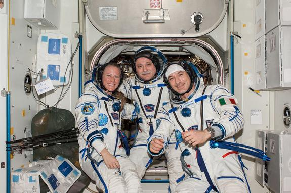 Russian cosmonaut Fyodor Yurchikhin (center), Expedition 37 commander; along with NASA astronaut Karen Nyberg and European Space Agency astronaut Luca Parmitano pose for a crew portrait while wearing their Russian Sokol spacesuits.