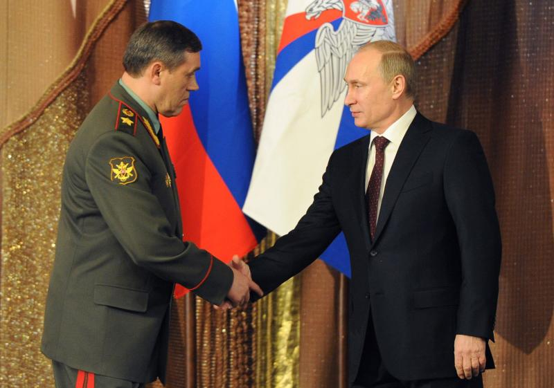 Russian President Vladimir Putin, right, shakes hands with Chief of the General Staff of the Russian Armed Forces Col. Gen. Valery Gerasimov during a meeting with the top military brass in Moscow, Russia, Tuesday, Dec. 10, 2013. President Vladimir Putin has ordered Russia's armed forces to expand their presence in the Arctic region as part of efforts to revive the nation's military might. (AP Photo/RIA-Novosti, Mikhail Klimentyev, Presidential Press Service)