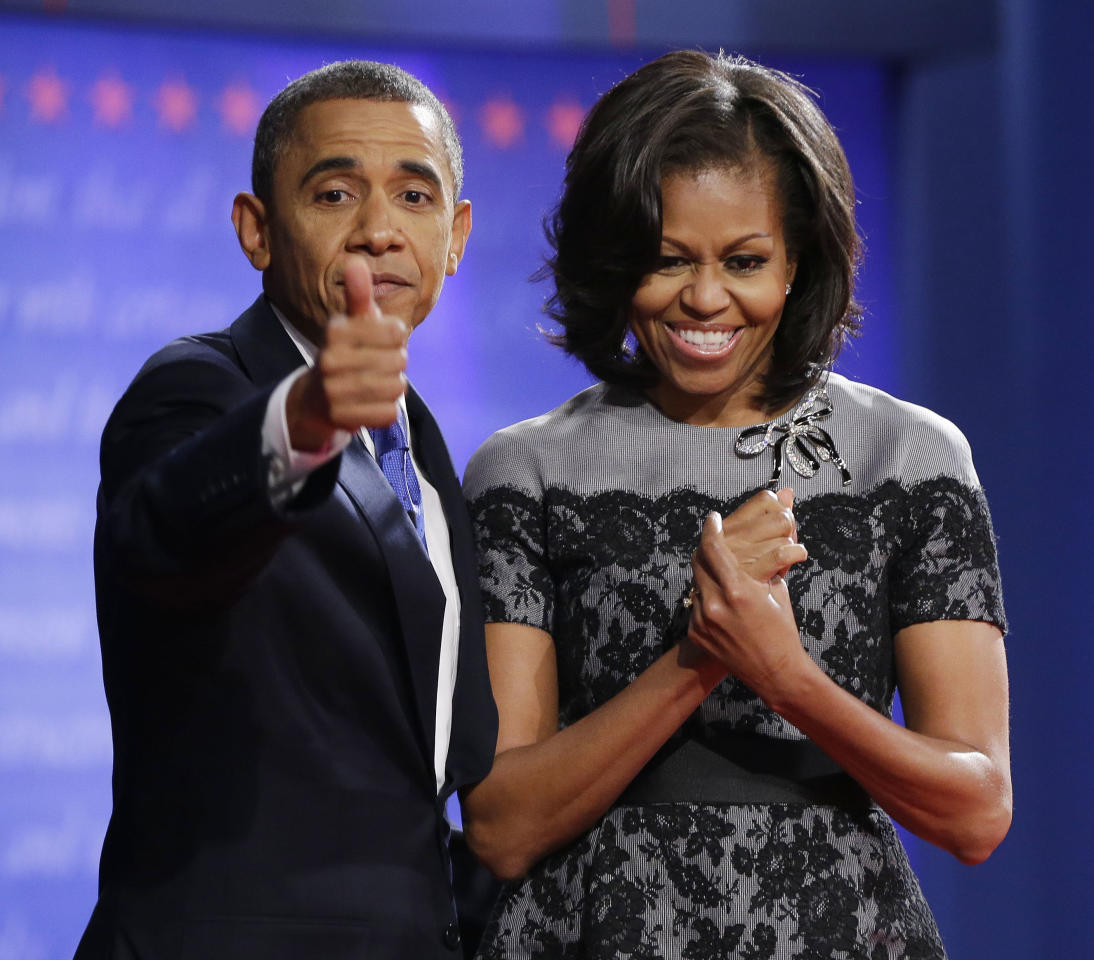 President Barack Obama, left, gives a thumbs-up as he is joined on stage by first lady Michelle Obama, right, at the end of the last debate against Republican presidential candidate, former Massachusetts Gov. Mitt Romney at Lynn University, Monday, Oct. 22, 2012, in Boca Raton, Fla. (AP Photo/Pablo Martinez Monsivais)