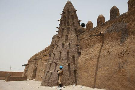 A UN peacekeeper from Burkina Faso stands guard at the Djinguereber mosque, built in the 14th century, during a visit by a UN delegation on election day in Timbuktu, Mali, July 28, 2013.  REUTERS/Joe Penney/Files