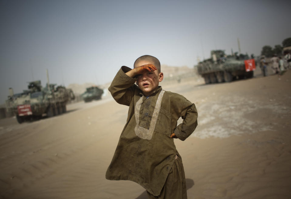 A child looks on as military vehicles of 5th Striker Brigades drive past his village on the outskirts of Spin Boldak, about 100 kilometers (63 miles, File) southeast of Kandahar, Afghanistan, on Aug. 6, 2009. (AP Photo/Emilio Morenatti, File)