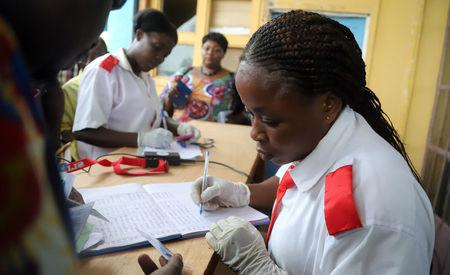 A Congolese health worker records medical data of passengers at the airport in Mbandaka, Democratic Republic of Congo May 19, 2018. REUTERS/Kenny Katombe