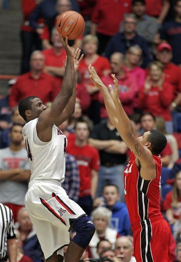 Arizona's Soloman Hill, left, shoots for three points against the attempted defense of Utah's Jordan Loveridge, right, during the second half of an NCAA college basketball game at McKale Center in Tucson, Ariz., Jan. 5, 2013. Arizona won 60 -57. (AP Photo/John Miller)