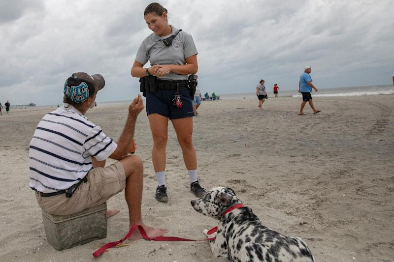 A North Myrtle Beach Police officer warns a beachgoer about the dangers of remaining on the beach as Hurricane Florence moves closer and conditions worsen in North Myrtle Beach, South Carolina (AFP Photo/Alex Edelman)