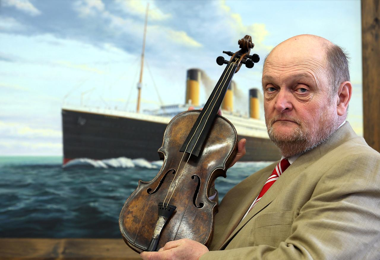 DEVIZES, ENGLAND - APRIL 15:  Auctioneer Alan Aldridge of auctioneers Henry Aldridge & son holds the violin of Wallace Hartley, the instrument he played as the band leader of the Titanic, on the 101st anniversary of the sinking of the ship, April 15, 2013 in Devizes, England.  The auction house, which specializes in Titanic memorabilia and is having an associated sale on Saturday, spent seven years proving the violin was genuine and belonged to Wallace Hartley, who with his orchestra, famously played on as the ship sank in April 1912, and were among the 1,500 who died. Long thought to have been either lost at sea or stolen, it is being described, as far as Titanic memorabilia goes, as one the most important pieces that has ever come up for sale. Thought to be worth a six-figure sum, it is the property of an unidentified individual in Lancashire and will be displayed to the public all week, but Aldridge's have not yet confirmed when it is likely to go on sale.  (Photo by Matt Cardy/Getty Images)