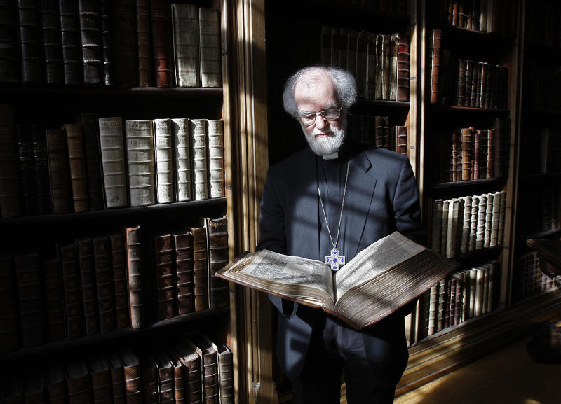 FILE - In this file photo dated Wednesday, May 25, 2011, then Archbishop of Canterbury Dr Rowan Williams poses with a 400-year old King James Bible at his London residence, Lambeth Palace.  According to a statement from the London Museum released Sunday April 16, 2017, the remains of five former archbishops of Canterbury were discovered during renovation works inside a secret tomb beneath a building located next to Lambeth Palace, including the remains of Richard Bancroft who became archbishop in 1604 and played a major role in production of the King James Bible. (AP Photo/Akira Suemori, FILE)