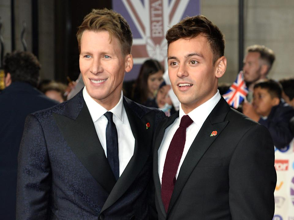 Dustin Lance Black and Tom Daley in suits on a red carpet