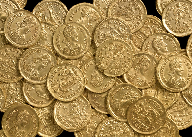 In this undated photo released by St Albans City and District Council on Wednesday, Oct. 17, 2012, late Roman gold coins, examples of the solidus, a high-value coin struck in the late fourth century, are photographed before going on display at the Verulamium Museum, St Albans, England. A curator at the museum says the coins, found on private land north of St. Albans, would have been used for major transactions such as buying land or ship cargoes. (AP Photo/St Albans City and District Council)