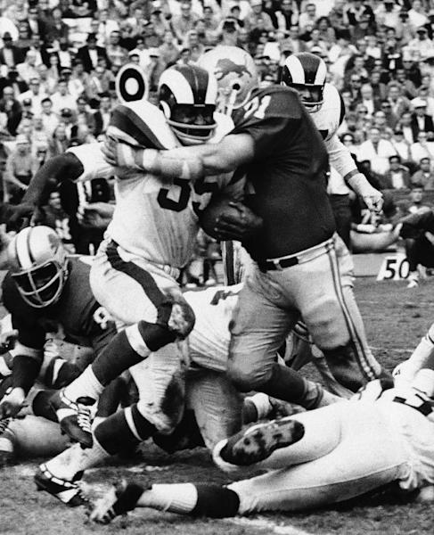 FILE - In this Nov. 3, 1968 file photo, Los Angeles Rams' Henry Dyer, center left, is hit by Detroit Lions' Alex Karras (71) during an NFL football game in Los Angeles. Karras and his wife, Susan Clark, are two of 119 people who filed suit Thursday, April 12, 2012, in U.S. District Court in Philadelphia, the latest complaint brought against the NFL by ex-players who say the league didn't do enough to protect them from head injuries. (AP Photo/File)