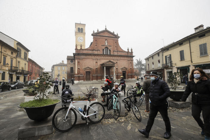 People and cyclists relax in front of the San Biagio church in Codogno, northern Italy, Sunday, Feb. 21, 2021. The first case of locally spread COVID-19 in Europe was found in the small town of Codogno, Italy one year ago on February 21st, 2020. The next day the area became a red zone, locked down and cutoff from the rest of Italy with soldiers standing at roadblocks keeping anyone from entering of leaving. (AP Photo/Luca Bruno)