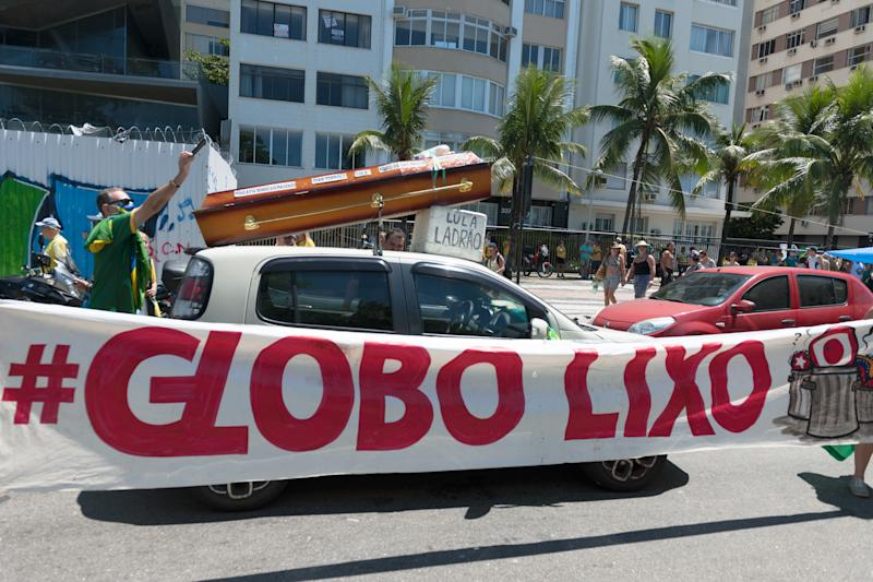 "RIO DE JANEIRO, BRAZIL - MARCH 15: A sign reading ""Globo lixo"" (in English ""Globo garbage"") in reference to the broadcaster Rede Globo is seen during a peaceful demonstration against Congress and Brazilian politicians in Copacabana, on March 15, 2020 in Rio de Janeiro, Brazil. (Photo by Alessandro Dahan/Getty Images)"