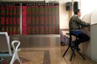 An investor sits next to a stock quotation board at a brokerage office in Beijing