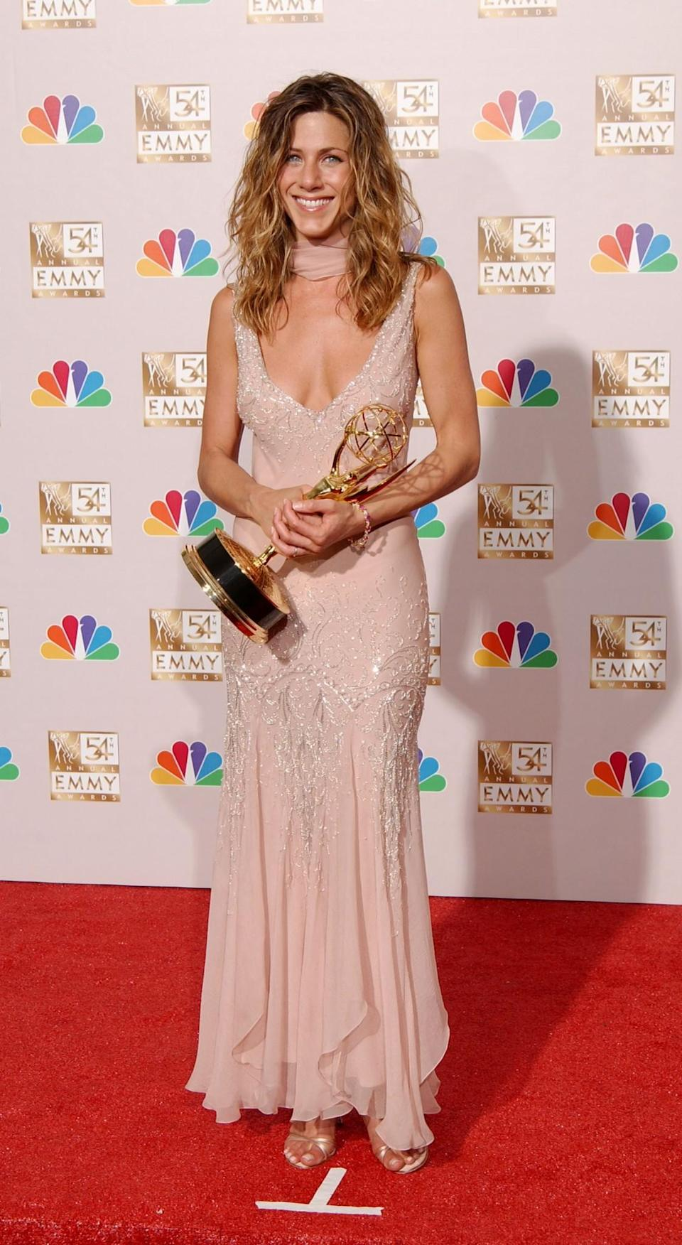 <p>Jennifer couldn't hide her grin after winning an Emmy in a blush pink low-cut gown and chic scarf. <i>[Photo: Getty]</i> </p>