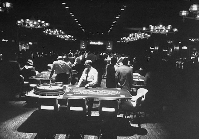Idling croupiers (in shirtsleeves) dawdled behind their roulette tables because few customers were placing bets in The Dunes two weeks after opening night.
